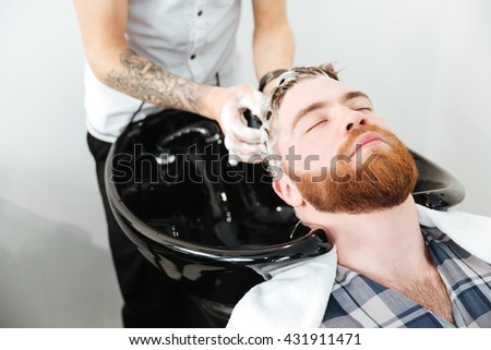Barber washing head client in barbershop