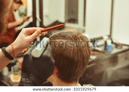 Barbershop. Close-up of man haircut, master does the hair styling in barber shop. Toned vintage photos.