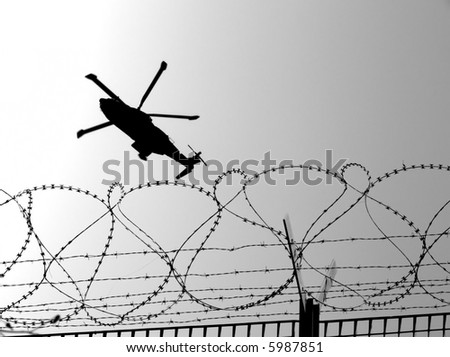 Barbwire and military helicopter in mission of war - stock photo
