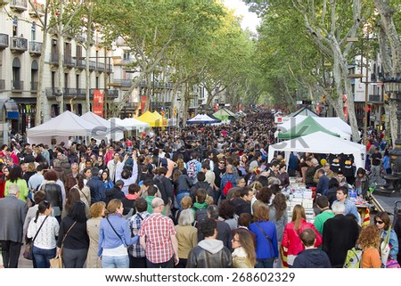 BARCELONA - APRIL 23: People in La Rambla during Diada de Sant Jordi or Saint George's Day, on April 23, 2013, in Barcelona, Spain. Traditionally, men gave women roses, and women gave men a book. - stock photo