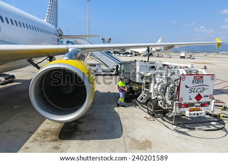 BARCELONA- AUGUST 5: Airbus A320 of the Vueling Airlines receiving fuel from tanker truck at Barcelona International Airport on August 5, 2014 in Barcelona, Catalonia, Spain.  - stock photo