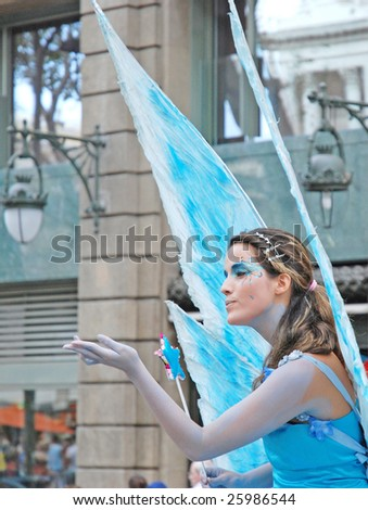 BARCELONA - AUGUST 14 : An unidentified young female performer dressed as butterfly greets visitors at student art festival in Barcelona, Spain August 14, 2008. - stock photo