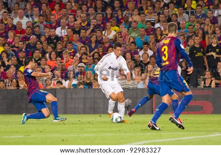 BARCELONA - AUGUST 17: Cristiano Ronaldo (Middle) in action during the Spanish Super Cup final match between FC Barcelona and Real Madrid, 3 - 2, on August 17, 2011 in Camp Nou, Barcelona, Spain. - stock photo