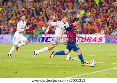 BARCELONA - AUGUST 17: Leo Messi (R) and Pepe Laveran (L) in action during the Spanish Supercup final match between FC Barcelona and Real Madrid, 3 - 2, on August 17, 2011 in Barcelona, Spain. - stock photo