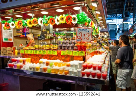 BARCELONA - AUGUST 31: Tourists in famous La Boqueria market on August 31, 2021 in Barcelona. One of the oldest markets in Europe that still exist. Established 1217. - stock photo