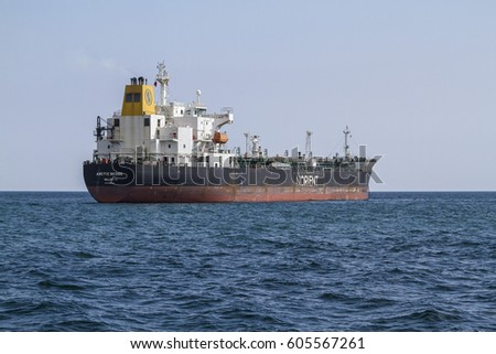 BARCELONA, CATALONIA, SPAIN - March, 12, 2017: A large heavy cargo ship arriving to Barcelona harbor to download its worthy materials.