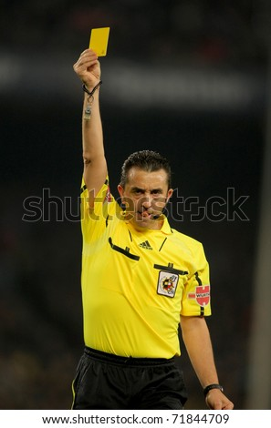 BARCELONA - FEB 20: Referee Ramirez Dominguez delivers yellow card during the match between FC Barcelona and Athletic de Bilbao at the Nou Camp Stadium on February 20, 2011 in Barcelona, Spain - stock photo