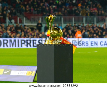 BARCELONA – JAN. 15: Club World Cup Footbal Trophy and FIFA World Player Gold Ball Award in Camp Nou stadium before the match between FC Barcelona vs Betis, on January 15, 2012, Barcelona, Spain. - stock photo