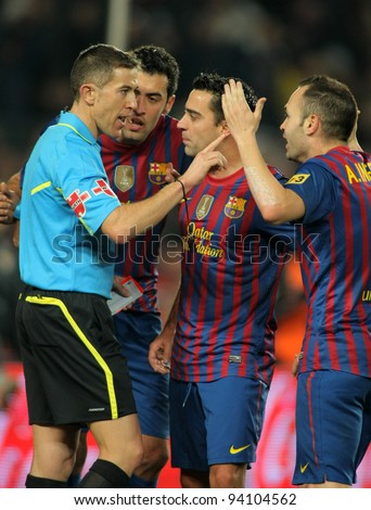 BARCELONA - JAN, 15: FC Barcelona players talk with the referee Iglesias Villanueva during the Spanish league match against R Betis at the Camp Nou stadium on January 15, 2012 in Barcelona, Spain - stock photo