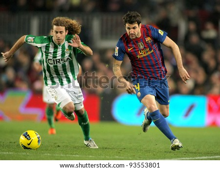 BARCELONA - JAN, 15: Jose Cañas(L) of Real Betis vies with Cesc Fabregas(R) of FC Barcelona during the Spanish league match at the Camp Nou stadium on January 15, 2012 in Barcelona, Spain - stock photo