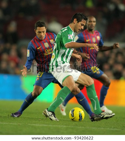 BARCELONA - JAN 15: Roque Santa Cruz(R) of Real Betis vies with Adriano Correia(L) of FC Barcelona during the Spanish league match at the Camp Nou stadium on January 15, 2012 in Barcelona, Spain - stock photo