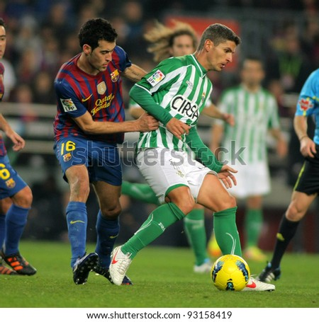BARCELONA - JAN, 15: Salva Sevilla(R) of Real Betis vies with Sergio Busquets(L) of FC Barcelona during the Spanish league match at the Camp Nou stadium on January 15, 2012 in Barcelona, Spain - stock photo