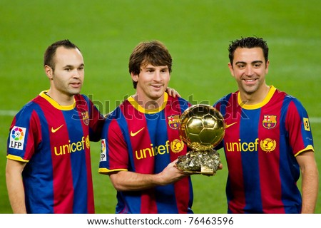 BARCELONA - JANUARY 12: Andres Iniesta (L), Leo Messi (middle) and Xavi Hernandez (R) offering the FIFA World Player Award to the FC Barcelona supporters, on January 12, 2011 in Barcelona (Spain). - stock photo