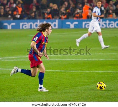 BARCELONA - JANUARY 16: Camp Nou soccer stadium, Spanish League match: FC Barcelona - Malaga, 4 - 1. In the picture, Carles Puyol in action. January 16, 2011 in Barcelona (Spain). - stock photo
