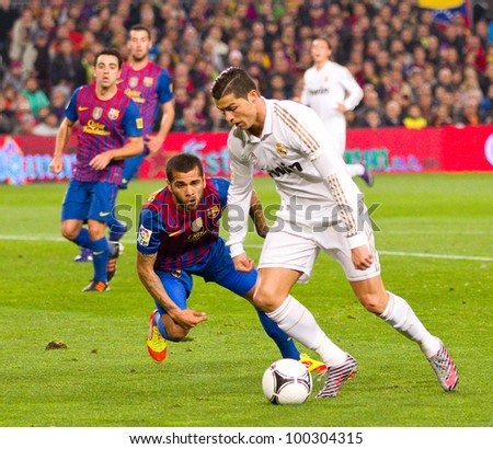 BARCELONA - JANUARY 25: Dani Alves and Cristiano Ronaldo (R) in action during the Spanish Cup match between FC Barcelona and Real Madrid, final score 2 - 2, on January 25, 2012, in Barcelona, Spain. - stock photo