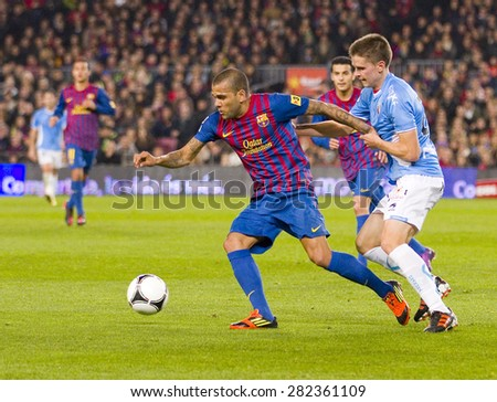 BARCELONA - JANUARY 4: Dani Alves (L) of Barcelona in action during the Spanish Cup match between FC Barcelona and Osasuna, final score 4 - 0, on January 4, 2012 in Camp Nou stadium, Barcelona, Spain. - stock photo