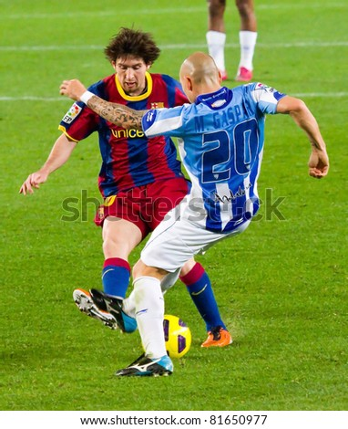 BARCELONA - JANUARY 16: Leo Messi (L) and Manolo Gaspar in action during Spanish League match between FC Barcelona and Malaga, 4 - 1. January 16, 2011 in Camp Nou stadium, Barcelona, Spain. - stock photo