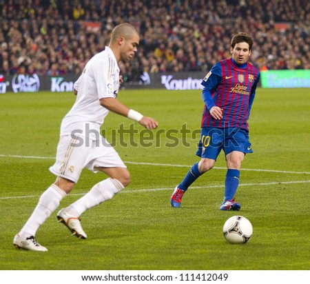 BARCELONA - JANUARY 25: Pepe Laveran (L) and Lionel Messi in action during the Spanish Cup match between FC Barcelona and Real Madrid, final score 2 - 2, on January 25, 2012, in Barcelona, Spain. - stock photo