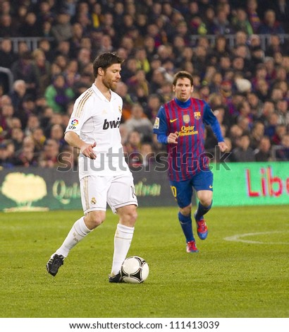 BARCELONA - JANUARY 25: Xabi Alonso (L) of Madrid in action during the Spanish Cup match between FC Barcelona and Real Madrid, final score 2 - 2, on January 25, 2012, in Barcelona, Spain. - stock photo