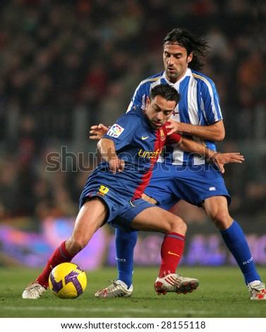 BARCELONA - JANUARY 17: Xavi Hernandez (L) of FC Barcelona in action during Spanish soccer league match between Barcelona and Deportivo La Coruna at Nou Camp stadium January 17, 2009 in Barcelona, Spain. - stock photo