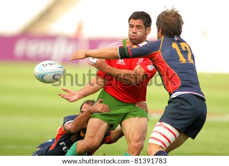 BARCELONA - JULY 9: David Mateus of Portugal passes the ball during the match of Rugby7 European Championship between Portugal and Spain at the Olympic Stadium in Barcelona, on July 9, 2011
