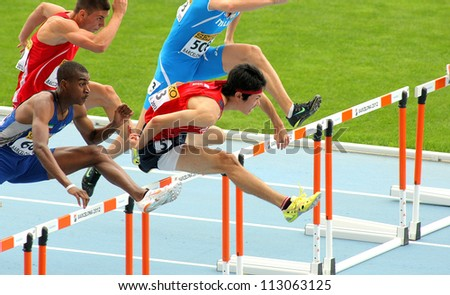 BARCELONA- JULY, 10: Shunya Takayama(R) of Japan during 110m men hurdles event of the 20th World Junior Athletics Championships at the Olympic Stadium on July 10, 2012 in Barcelona, Spain - stock photo