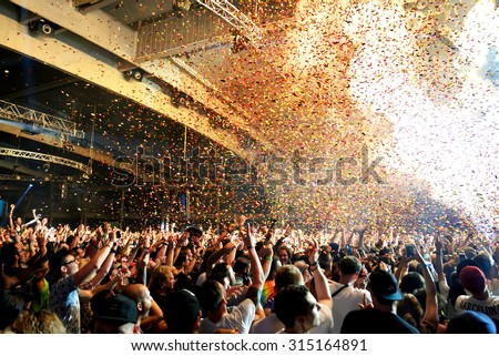 BARCELONA - JUN 19: Crowd in a concert, while throwing confetti from the stage at Sonar Festival on June 19, 2015 in Barcelona, Spain.
