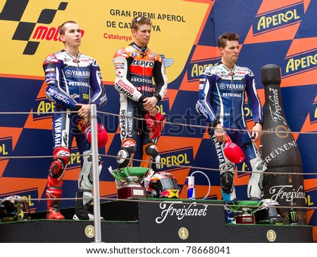 BARCELONA - JUNE 5: Casey Stoner (1st), Jorge Lorenzo (2nd) and Ben Spies (3dr) celebrating their trophies in the podium after the MotoGP Grand Prix of Catalonia, on June 5, 2011 in Barcelona, Spain. - stock photo