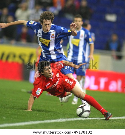 BARCELONA - MARCH 20: Perotti(D) of Sevilla falls beside of Baena(U) of Espanyol during a Spanish League match between Espanyol and Sevilla at the Estadi Cornella on March 20, 2010 in Barcelona, Spain