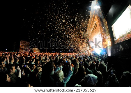 BARCELONA - MAY 23: Audience watch a concert, while throwing confetti from the stage at Heineken Primavera Sound 2013 Festival, Pitchfork Stage, on May 23, 2013 in Barcelona, Spain. - stock photo