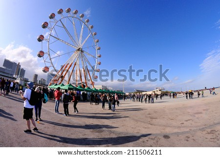 BARCELONA - MAY 24: People and a ferris wheel at Heineken Primavera Sound 2013 Festival on May 24, 2013 in Barcelona, Spain. People come up to the ferris wheel and watch the concerts from the heights. - stock photo