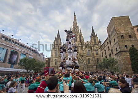 BARCELONA - MAY 23, 2015: People building a human tower, called castelling, among a large crowd of people in front of the cathedral of Barcelona, Spain on May 23, 2015. - stock photo