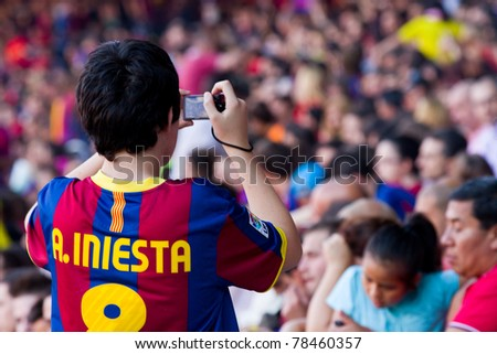 BARCELONA - MAY 13: Unidentified supporter shoot a photo during the FC Barcelona Spanish League Championship victory celebration in Camp Nou stadium, on May 13, 2011 in Barcelona, Spain. - stock photo