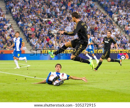 BARCELONA - OCTOBER 2: Cristiano Ronaldo of RM jumping at the Spanish League match between RCD Espanyol and Real Madrid, final score 0 - 4, on October 2, 2011 in Cornella stadium, Barcelona, Spain. - stock photo