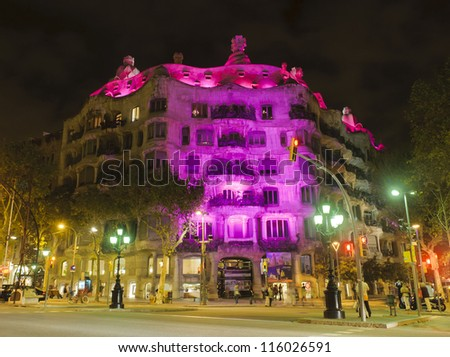 BARCELONA - OCTOBER 18: La Pedrera or Casa Mila designed by Antonio Gaudi, with pink illumination to commemorate the breast cancer day, on October 18, 2012, Barcelona. - stock photo
