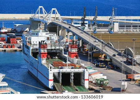 BARCELONA - SEPTEMBER 15: Loading of trucks onto Acciona ship in Barcelona port, September 15, 2011, Barcelona, Spain. Acciona, S.A. is a Spanish conglomerate group