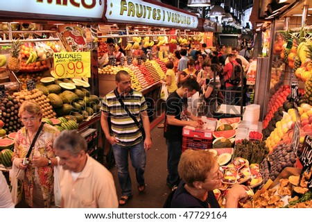 BARCELONA - SEPTEMBER 9: Tourists in famous La Boqueria market on September 9, 2009 in Barcelona. One of the oldest markets in Europe that still exist. Established 1217. - stock photo