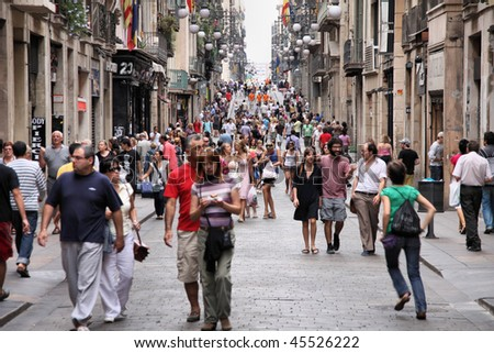 BARCELONA - SEPTEMBER 13: Tourists strolling the famous Carrer de Ferran on September 13, 2009 in Barcelona. It is one of the busiest pedestrian areas in Barcelona, connecting famous Rambla boulevard. - stock photo