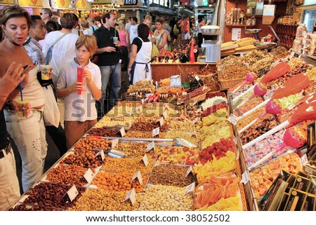 BARCELONA - SEPTEMBER 9: Tourists visit famous La Boqueria market September 9, 2009 in Barcelona. It is one of the oldest markets in Europe that still exist since 1217. - stock photo