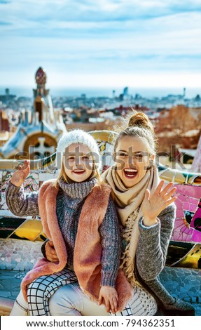 Barcelona signature style. Portrait of happy trendy mother and daughter tourists at Guell Park in Barcelona, Spain handwaving while sitting on a bench