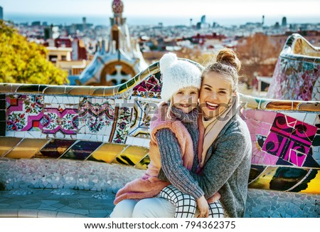 Barcelona signature style. Portrait of smiling modern mother and daughter tourists at Guell Park in Barcelona, Spain hugging while sitting on a bench