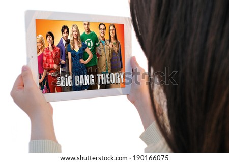 BARCELONA, SPAIN - APR 21, 2014: Unrecognizable woman watches, on her Apple Ipad, The Big Bang Theory, a famous American sitcom (situation comedy), isolated on white background. - stock photo