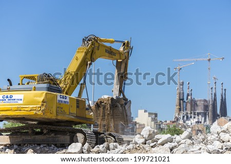 Barcelona, Spain - 28 April, 2014: excavator placing sand or debris on a truck with the Sagrada Familia in the background.  - stock photo