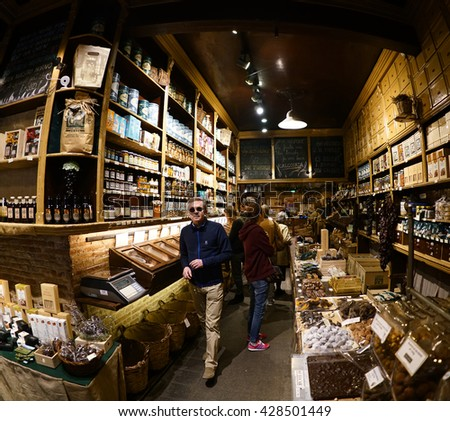 Barcelona, Spain - April 07, 2016:People buying food inside in small store. dried fruit and nuts for sale at a market stall