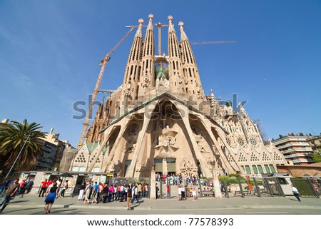 BARCELONA, SPAIN - APRIL 12: Tourists looking Sagrada Familia in April 12, 2011 in Barcelona, Spain.  Expiatory Church of  Holy Family (Sagrada Familia) by architect Gaudi, building is begun in 1882 - stock photo