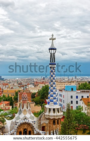 Barcelona, Spain - August 13, 2010: Entrance building in Park Guell in Barcelona in Spain. Designed in the form of gingerbread by Antoni Gaudi, Spanish artist. With a view on skyline of Barcelona city - stock photo