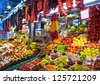 BARCELONA, SPAIN - AUGUST 31: Famous La Boqueria market with vegetables and fruits on August 31, 2012 in Barcelona, Spain. One of the oldest markets in Europe that still exist. Established 1217. - stock photo
