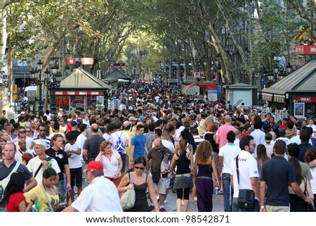 BARCELONA, SPAIN - AUGUST 14: Famous street La Rambla, August 14, 2009 in Barcelona, Spain. Thousands of people walk daily by this popular pedestrian area 1.2 kilometer long. - stock photo