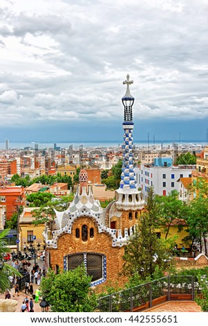 Barcelona, Spain - August 13, 2010: Tourists and Entrance building in Park Guell in Barcelona in Spain. It was designed by Antoni Gaudi, Spanish artist. With a view on skyline of Barcelona city. - stock photo