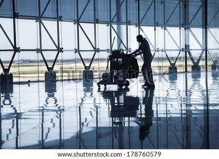 BARCELONA, SPAIN - CIRCA MAY 2010: Cleaning staff  at new Barcelona Terminal airport hall. Building architetcural detail designed by Richard Bofill architect. - stock photo